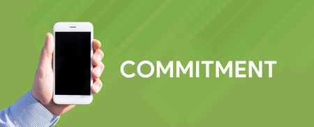 Smart phone in hand front of green background and written COMMITMENT