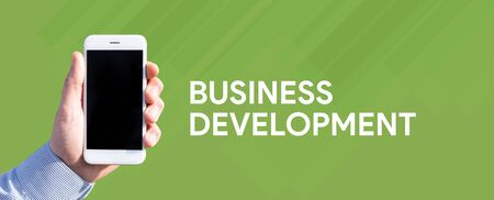 Smart phone in hand front of green background and written BUSINESS DEVELOPMENT