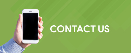 Smart phone in hand front of green background and written CONTACT US Stock Photo