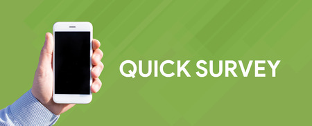Smart phone in hand front of green background and written QUICK SURVEY Stock Photo