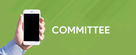 comité d entreprise: Smart phone in hand front of green background and written COMMITTEE