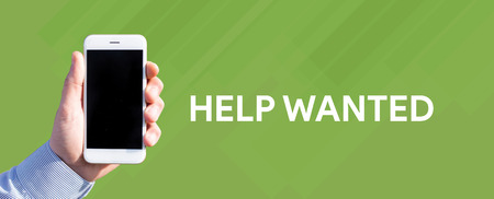 Smart phone in hand front of green background and written HELP WANTED