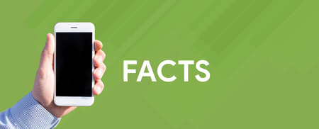 exactitude: Smart phone in hand front of green background and written FACTS