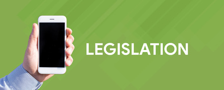 legislation: Smart phone in hand front of green background and written LEGISLATION