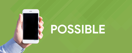 unachievable: Smart phone in hand front of green background and written POSSIBLE