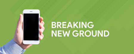 breaking new ground: Smart phone in hand front of green background and written BREAKING NEW GROUND