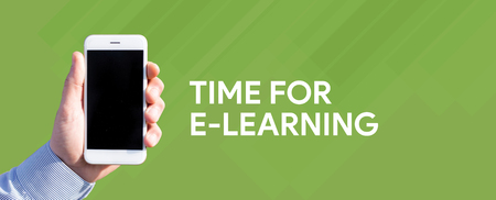 instances: Smart phone in hand front of green background and written TIME FOR E-LEARNING Stock Photo