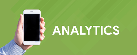 Smart phone in hand front of green background and written ANALYTICS