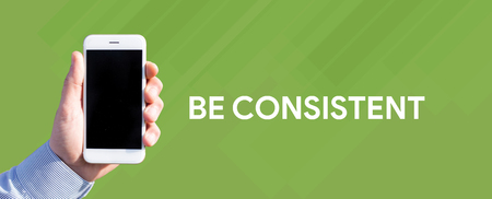 consistency: Smart phone in hand front of green background and written BE CONSISTENT