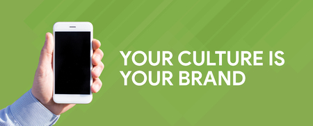 Smart phone in hand front of green background and written YOUR CULTURE IS YOUR BRAND
