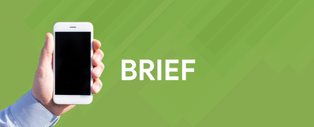 brief: Smart phone in hand front of green background and written BRIEF