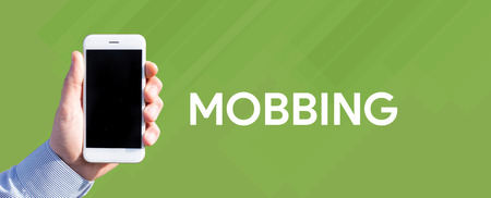 mobbing: Smart phone in hand front of green background and written MOBBING