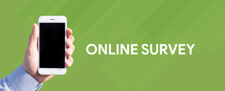 Smart phone in hand front of green background and written ONLINE SURVEY