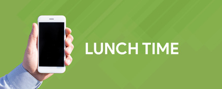 breakout: Smart phone in hand front of green background and written LUNCH TIME Stock Photo