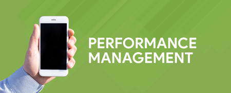 Smart phone in hand front of green background and written PERFORMANCE MANAGEMENT Stock Photo