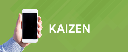 Smart phone in hand front of green background and written KAIZEN