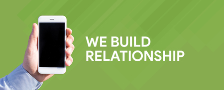 Smart phone in hand front of green background and written WE BUILD RELATIONSHIP Stock Photo