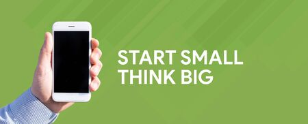 Smart phone in hand front of green background and written START SMALL THINK BIG Stock Photo