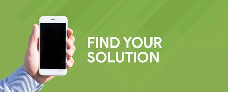Smart phone in hand front of green background and written FIND YOUR SOLUTION Stock Photo