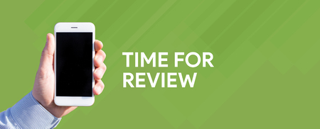 reassessment: Smart phone in hand front of green background and written TIME FOR REVIEW