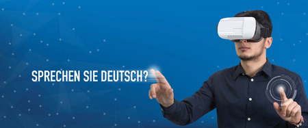 deutsch: Future Technology and Business Concept: The Man with Glasses of Virtual Reality and touching SPRECHEN SIE DEUTSCH? button Stock Photo