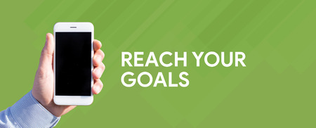Smart phone in hand front of green background and written REACH YOUR GOALS