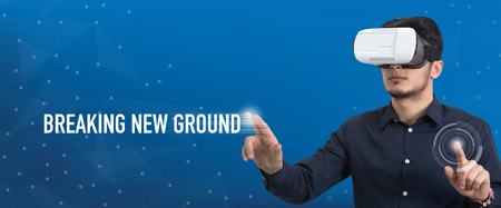 breaking new ground: Future Technology and Business Concept: The Man with Glasses of Virtual Reality and touching BREAKING NEW GROUND button Stock Photo