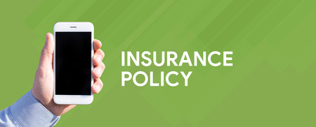 Smart phone in hand front of green background and written INSURANCE POLICY