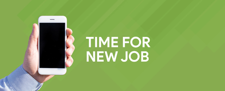 Smart phone in hand front of green background and written TIME FOR NEW JOB Stock Photo