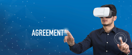 technology agreement: Future Technology and Business Concept: The Man with Glasses of Virtual Reality and touching AGREEMENT button