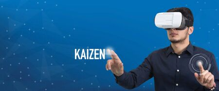 Future Technology and Business Concept: The Man with Glasses of Virtual Reality and touching KAIZEN button Stock Photo