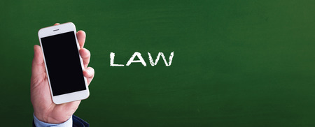 Smart phone in hand front of blackboard and written LAW