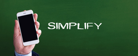 pragmatic: Smart phone in hand front of blackboard and written SIMPLIFY Stock Photo
