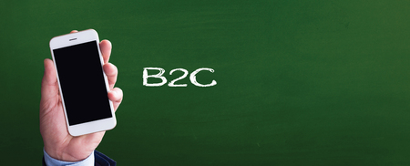 b2c: Smart phone in hand front of blackboard and written B2C