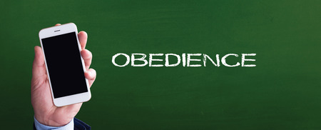 obedience: Smart phone in hand front of blackboard and written OBEDIENCE