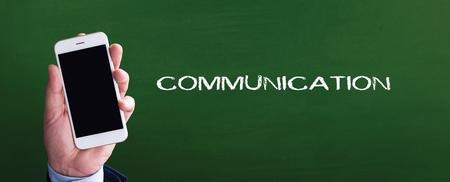 comunicación escrita: teléfono inteligente en la mano delante de la comunicación escrita y pizarra