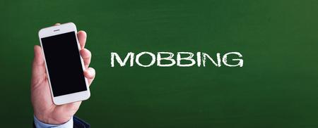mobbing: Smart phone in hand front of blackboard and written MOBBING