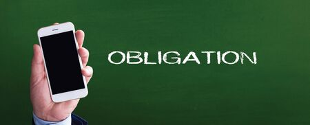obligated: Smart phone in hand front of blackboard and written OBLIGATION