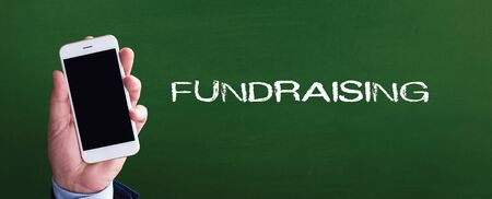 Smart phone in hand front of blackboard and written FUNDRAISING