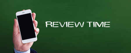 reassessment: Smart phone in hand front of blackboard and written REVIEW TIME