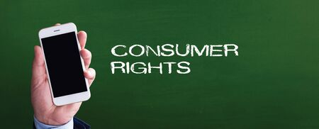 consumer rights: Smart phone in hand front of blackboard and written CONSUMER RIGHTS