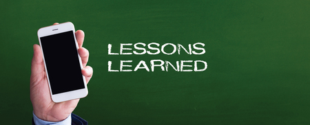 Smart phone in hand front of blackboard and written LESSONS LEARNED