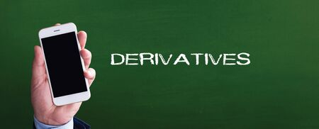 derivative: Smart phone in hand front of blackboard and written DERIVATIVES