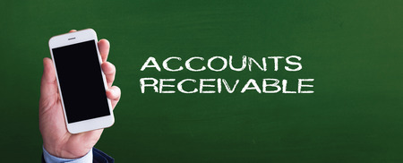 accounts payable: Smart phone in hand front of blackboard and written ACCOUNTS RECEIVABLE Stock Photo