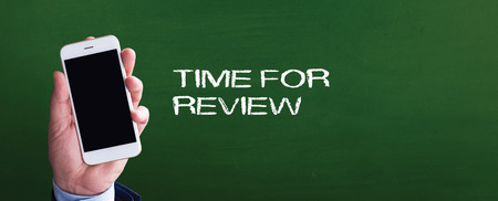 Smart phone in hand front of blackboard and written TIME FOR REVIEW
