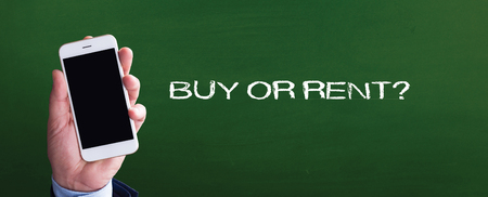 buying questions: Smart phone in hand front of blackboard and written BUY OR RENT?