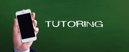 Smart phone in hand front of blackboard and written TUTORING