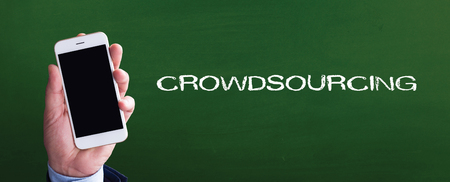crowd source: Smart phone in hand front of blackboard and written CROWDSOURCING