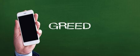 greed: Smart phone in hand front of blackboard and written GREED