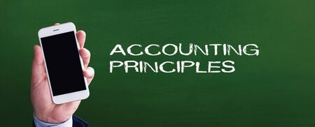principles: Smart phone in hand front of blackboard and written ACCOUNTING PRINCIPLES